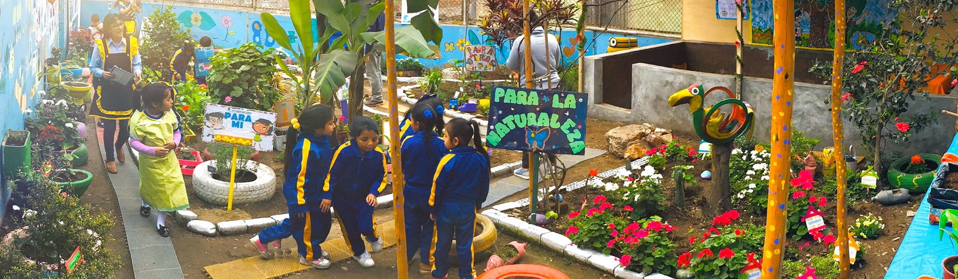 Alunos uniformizados e professores numa TiNi no pátio de uma escola. Há muitas plantas e flores nos canteiros e vasos