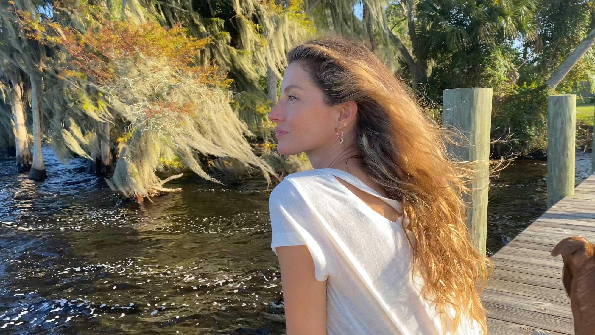 Gisele está sentada de lado, de camiseta branca, cabelos soltos, num píer, sobre um rio e árvores ao fundo