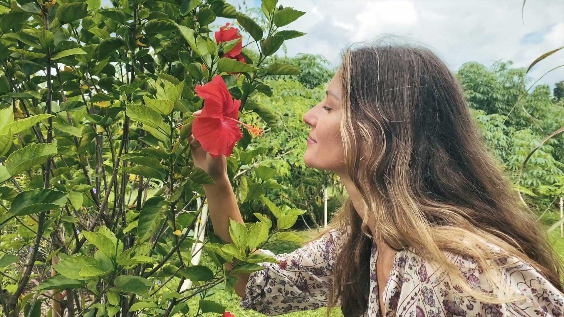 Gisele de perfil, cheira uma flor vermelha num arbusto