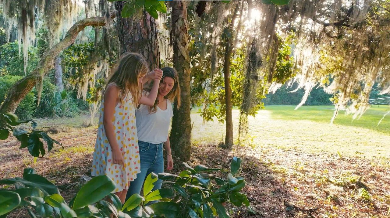 Gisele de mão dada com sua filha, que caminha sobre um tronco, em meio a natureza